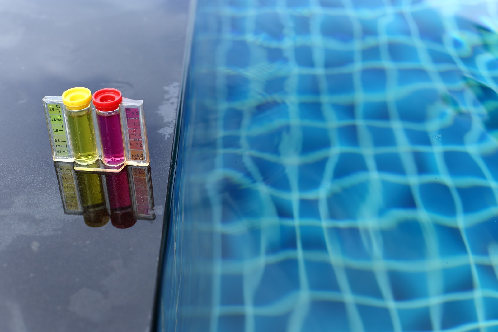 a yellow and pink test kit next to an inground pool checking for CYA levels in the water