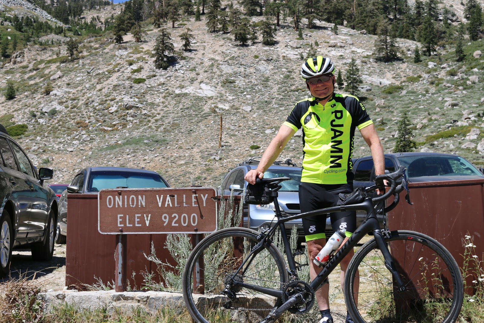 Cyclist at Onion Valley Road Elevation 9200 sign