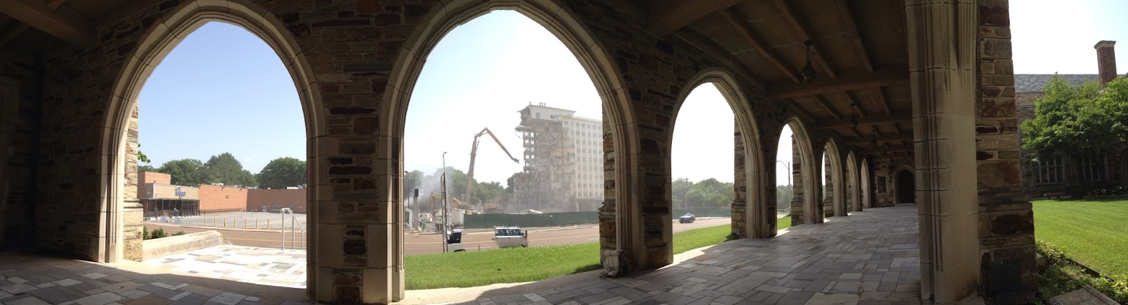 Panorama of 4 church arches and a building being destroyed across the street.