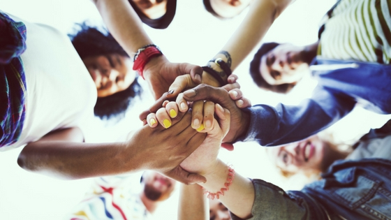 A group of people joining in a huddle grasping each others' hands.
