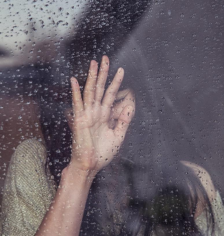 A picture containing person, rain, holding, water
