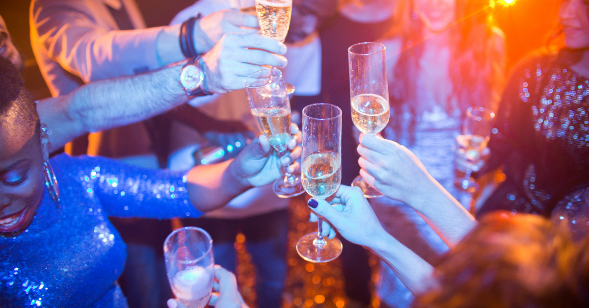 People raising a glass of champagne at a formal dance party