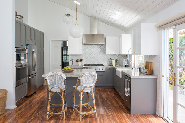 a beachy bright kitchen remodel from hgtv. white shaker upper cabinets are contrasted by grey shaker base cabinets. a warm wood floor keeps the space feeling like a traditional beach cottage