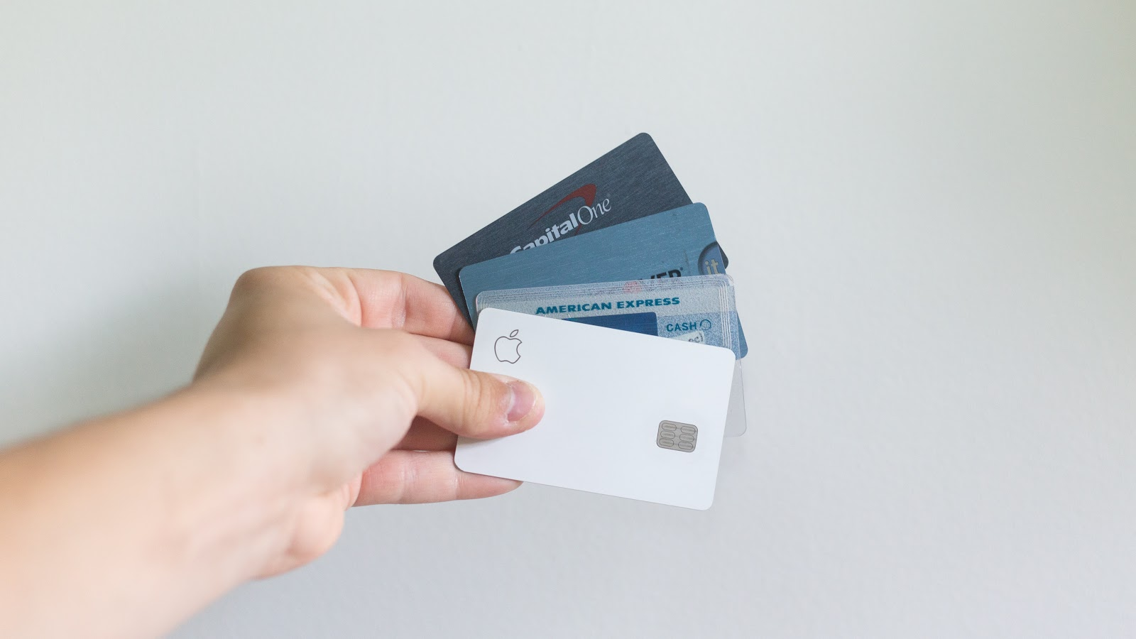 A hand holds four debit cards.