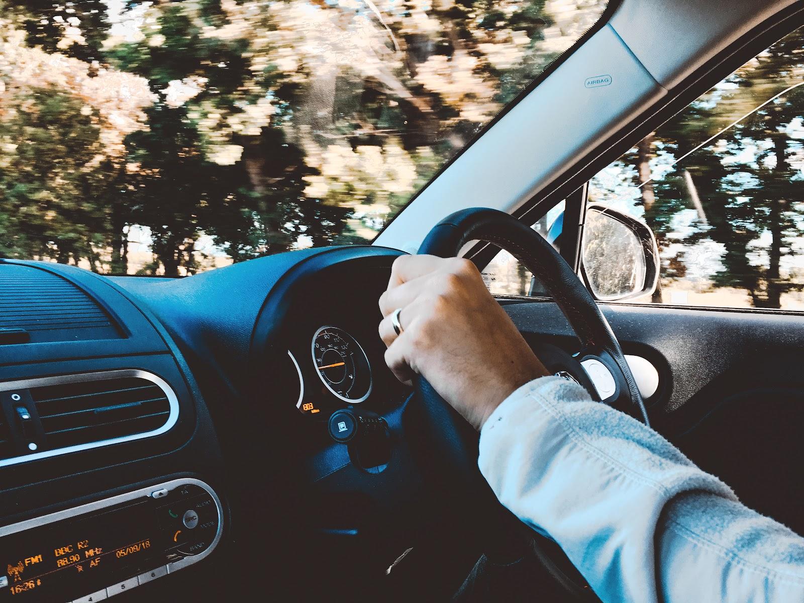Uma mão dirigindo um volante de carro.