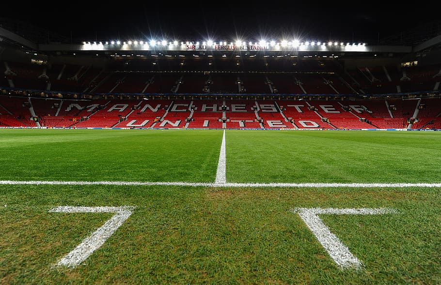 "An empty Old Trafford football stadium with the words ""Manchester United"" written on red seats"