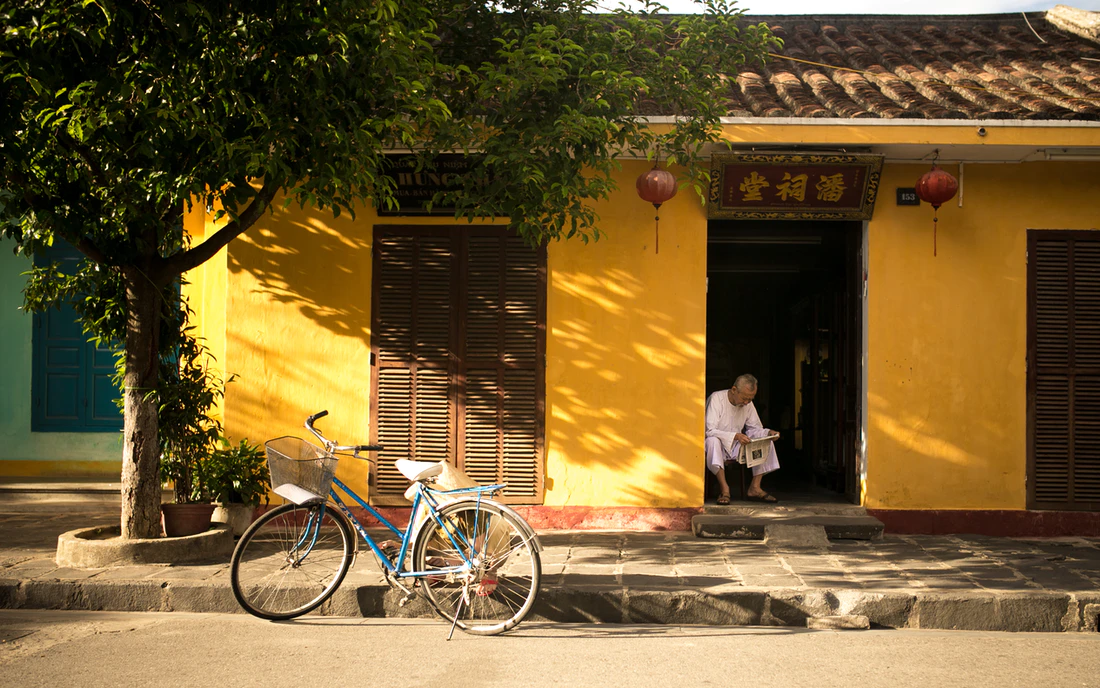a man reads a newspaper outside his house