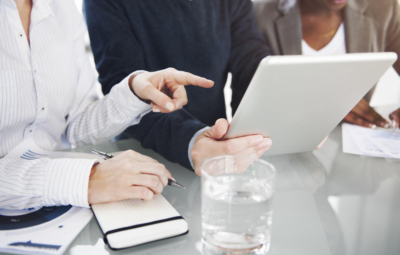 Uma pessoa segurando um tablet e uma mão do lado indicando para ele.