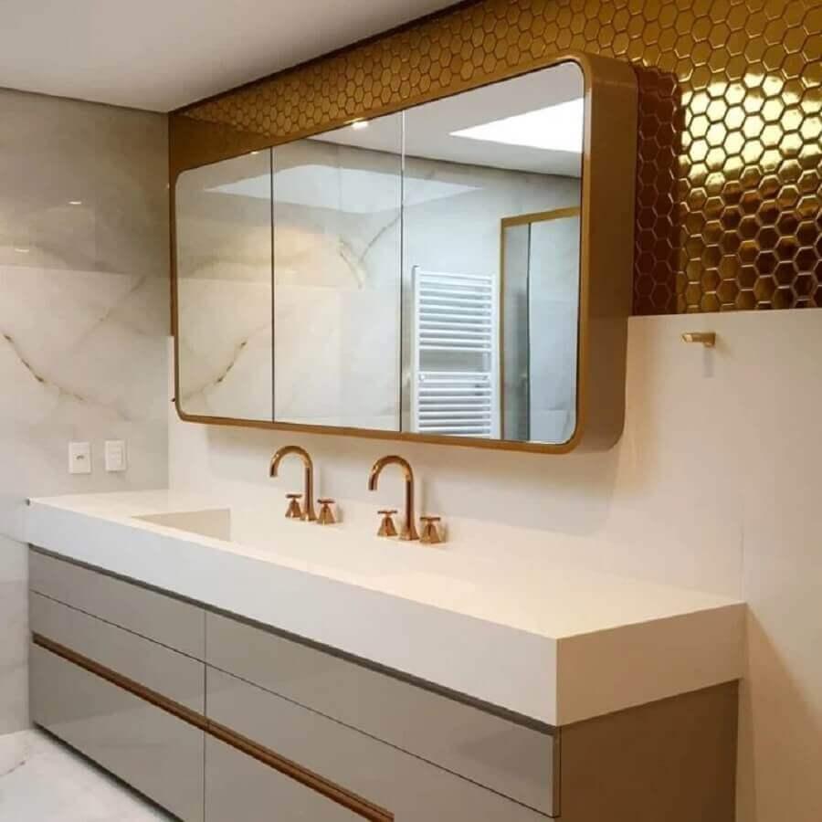 Banheiro com pastilha hexagonal dourada em meia parede e demais pintada de branca, armário cinza com bancada branca, torneira dourada e espelho com moldura dourada