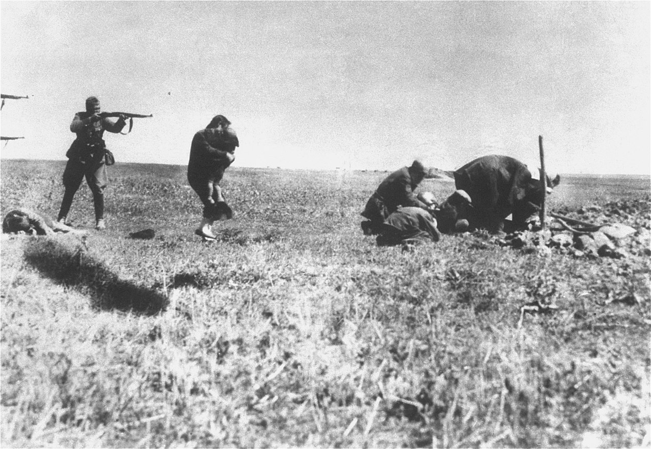 Photograph of a mass murder in progress, with Nazi soldiers about to murder a woman, child, and group of men.