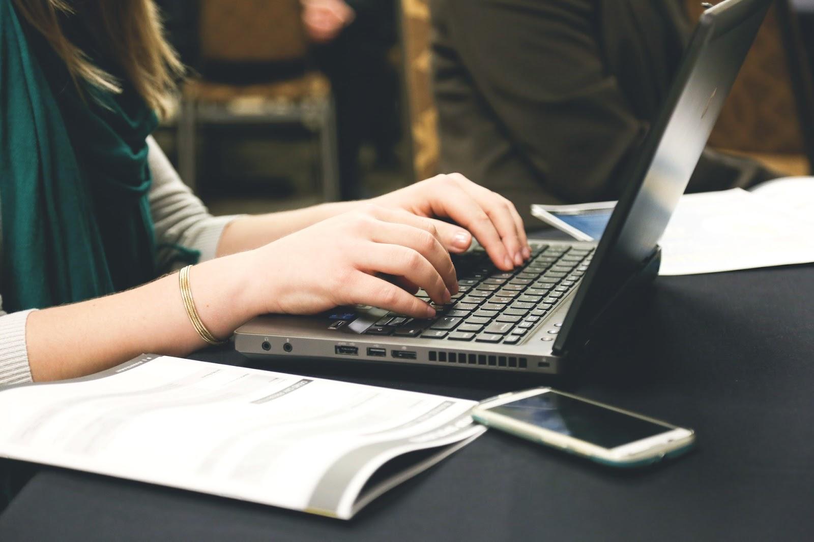 A mum sat at a laptop working as a copywriter.