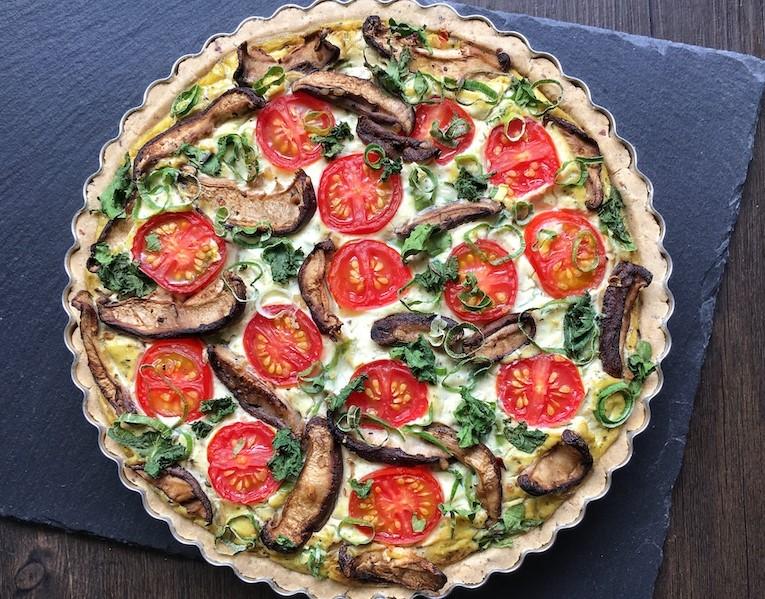 Quiche vegana vista de cima. Para a decoração foram utilizadas tiras de cogumelo, rodelas finas de tomate e cebolinha, criando uma bela composição em tons de verde e vermelho.