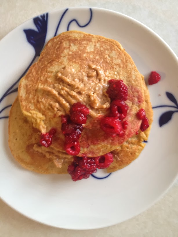 Gluten-free protein pancakes with organic raspberries, maple syrup, and peanut butter