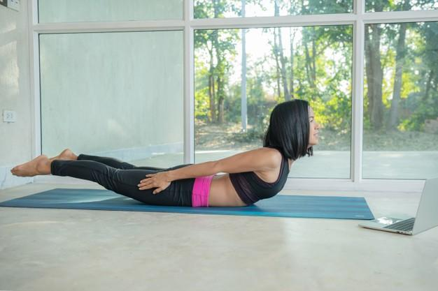 Sporty woman practicing yoga, back and buttock training pose, stretching watching fitness video tutorial online on laptop, doing workout at home sitting on mat in living room practicing Free Photo
