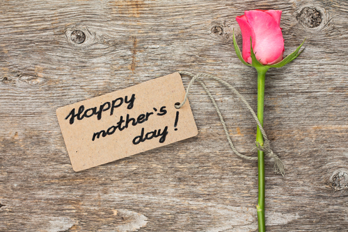 Pictured: A mother's day card with handwritten script proclaiming Happy Mother's Day with a single stem pink rose sitting next to it.