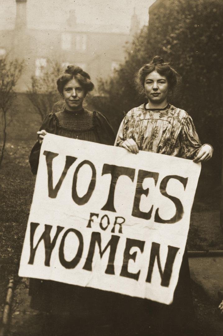 """foto em preto e branco de duas mulheres brancas de cabelos presos segurando um cartaz branco com os escritos """"Votes for women(Voto para as mulheres) em preto. Foto: http://www.hastingspress.co.uk/history/sufpix.htm"""