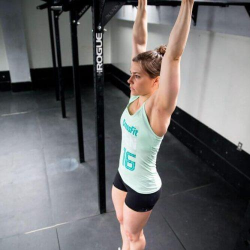 A lady is in shorts and tank-top. She has her arms up hanging from a bar above her head, arms fully extended. Her feet are not touching the floor.