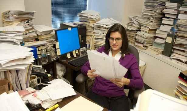 mulher segurando papel dentro de uma sala bagunçada cheia de papelada.