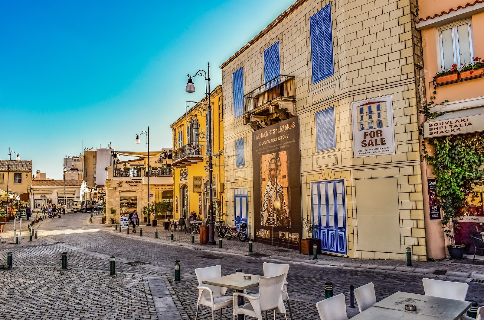 larnaca cyprus, small square and cobblestone roads. Whitewashed buildings, traditional architecture, empty tables. sunny day in cyprus