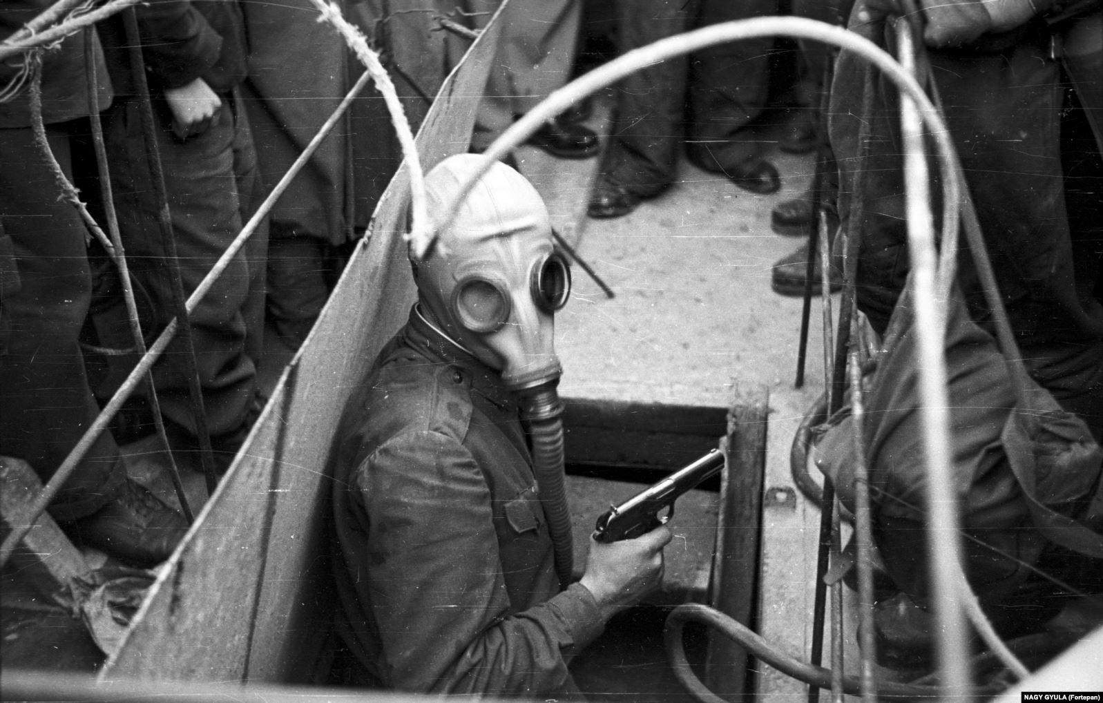 Человек с пистолетом вылезает из строящегося метро во время хаоса восстания 1956 года