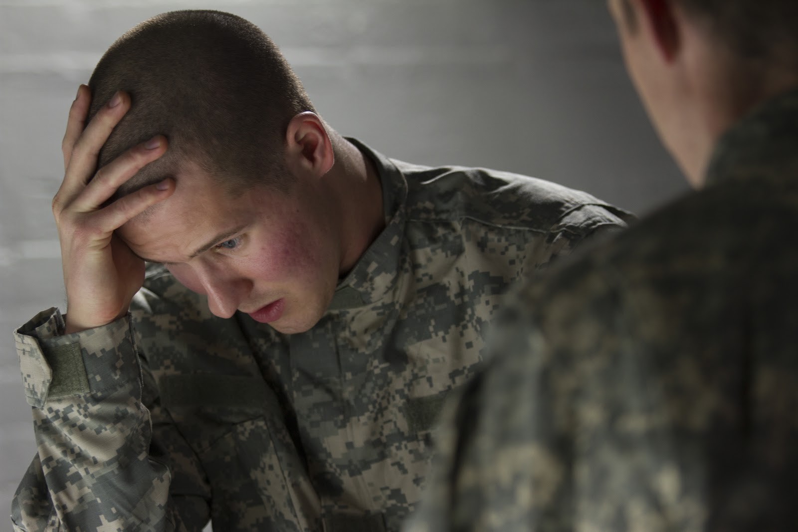A soldier with his head in his hands, speaking to another about PTSD