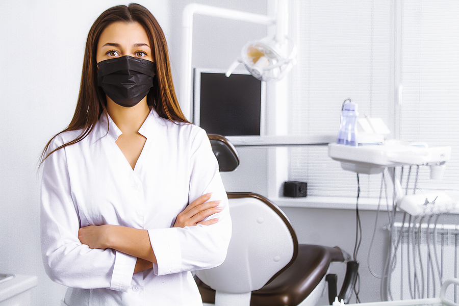 Dentist in her practice and wearing a face mask.