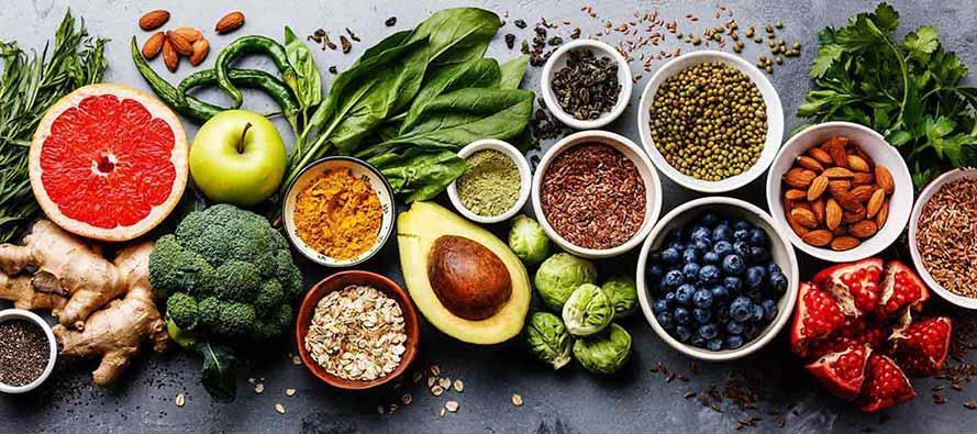 Choix d'une alimentation saine et propre : fruits, légumes, graines, superalimentation, céréales, légumes à feuilles sur fond gris