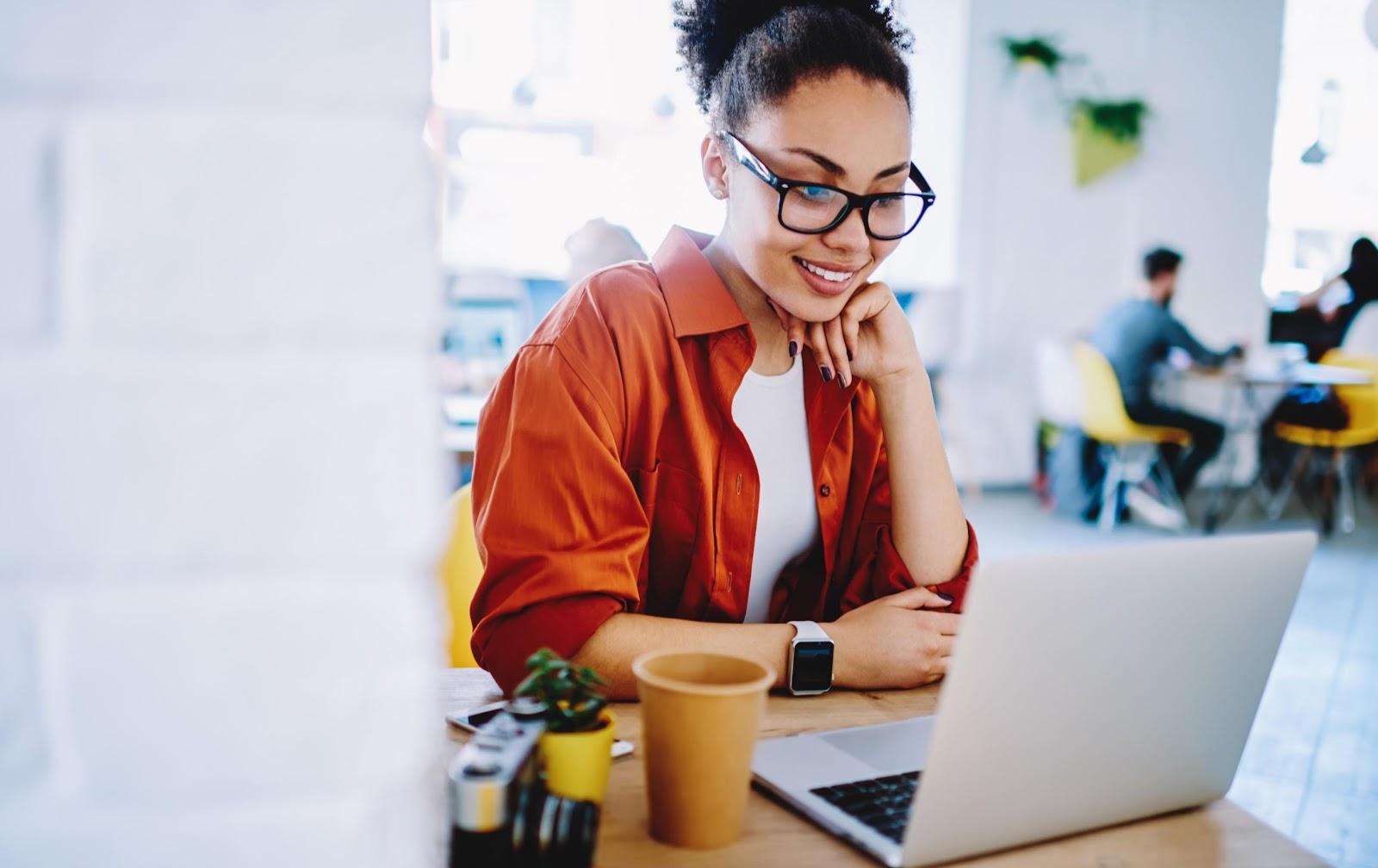 ositive dark skinned hipster girl enjoying friendly video call on laptop compute