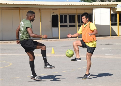 Two soccer players juggling a ball