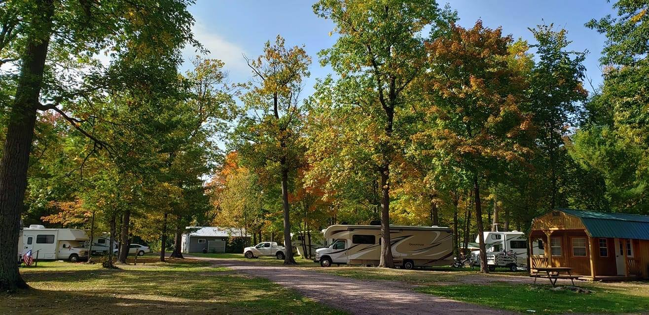 Campground filled with RVs and cabins in fall.