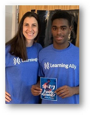 Reading Specialist Katherine York and eighth-grader Tristan stand in front of her classroom door.  They are both wearing bright blue Learning Ally t-shirts, and have big smiles on their faces.  Tristan is holding a copy of the book he read, Swing by Kwame Alexander.