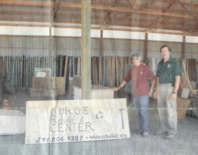 Bob Bryant and David Skakel stand next to the first Gorge Rebuild-it Center sign, in front of the new pole building