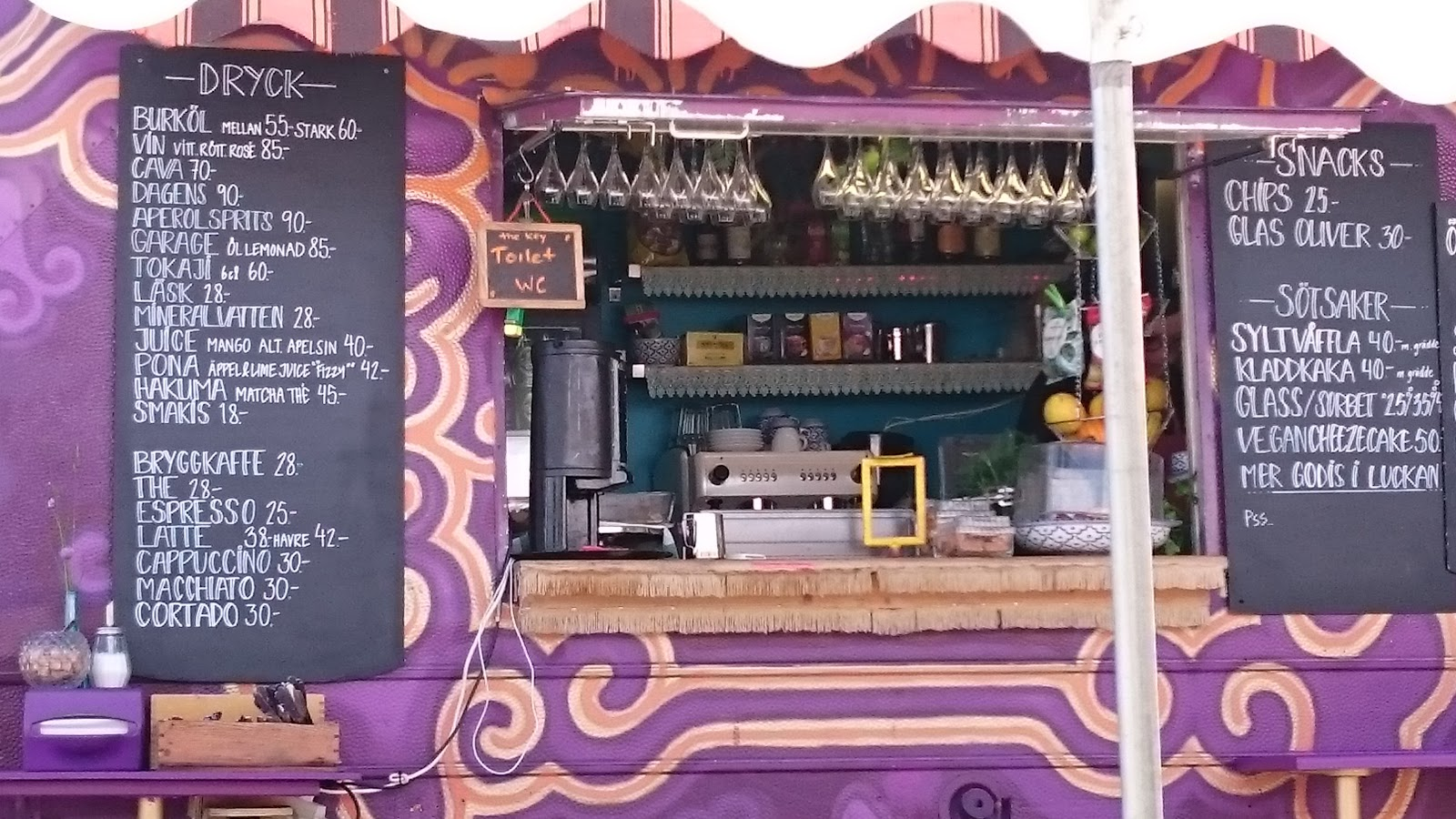 The image shows the front of the café. To the left of the window for ordering the drinks menu is displayed, and to the right is the snacks & fika menu.