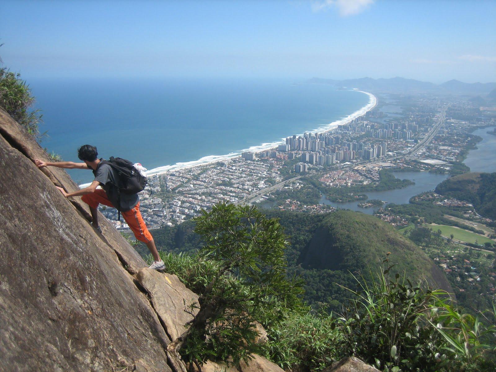 Homem escalando pedra no caminho de uma das trilhas do Rio de Janeiro.