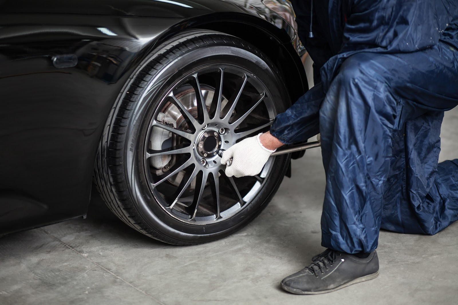 A mechanic fitting a new tyre onto a black car.