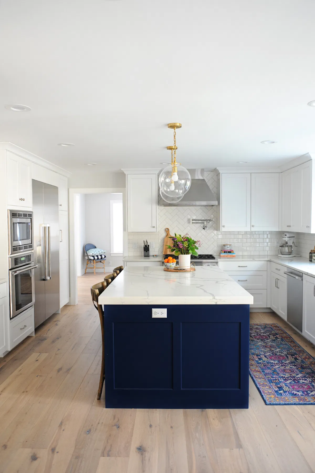 contemporary blue and white kitchen design with white shaker cabinets and a navy blue center island. blue and white cabinets are one of the best cabinet colors for 2020