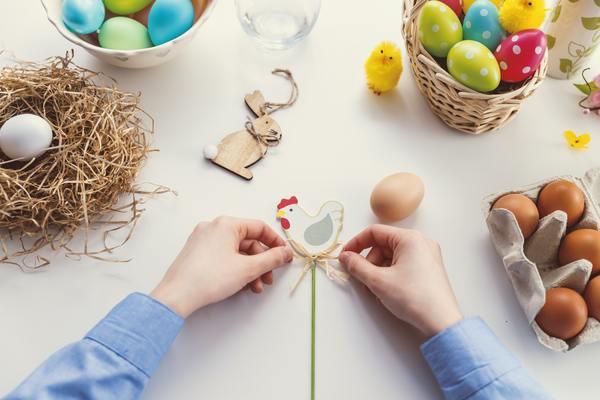 Mãos brancas segurando um doce em formato de galinha, ao lado de vários ovos de ovos coloridos em tema de páscoa
