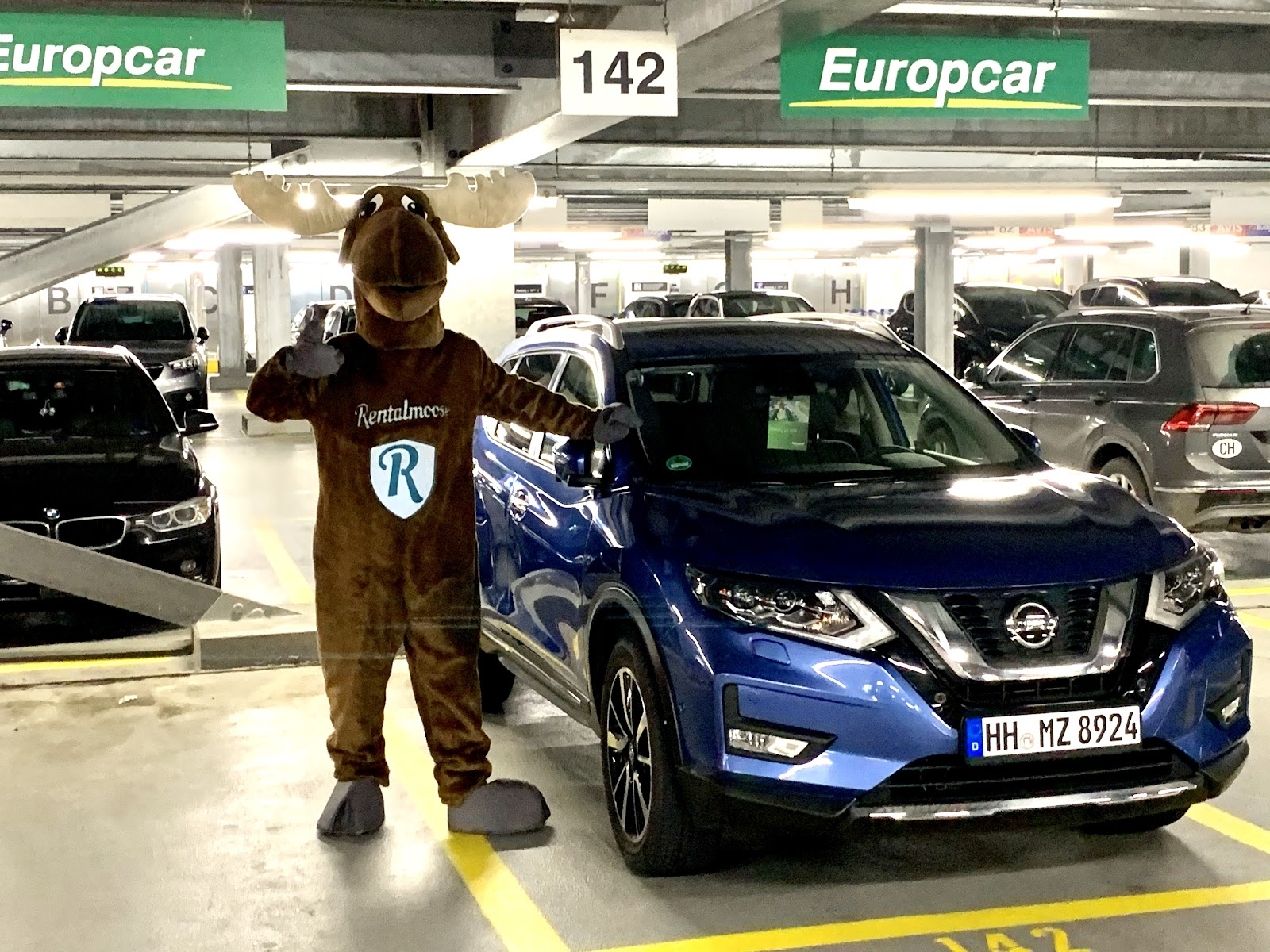 Rental Moose mascot posing in undeground garage, next to blue Nissan rental car by Europcar. Rental Moose is a global car rental broker which will help you get the best deal on your next rental car.