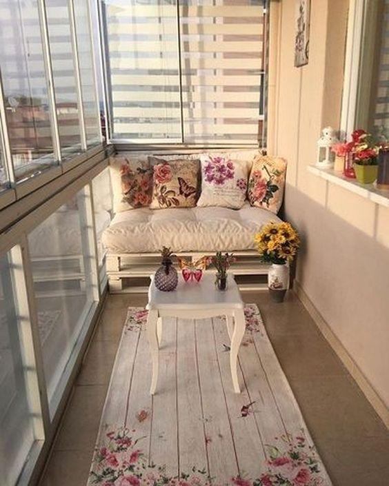 Varanda com decoração delicada, sofá de pallet com estofado branco e almofadas florais, tapete floral e mesinha de centro branca.