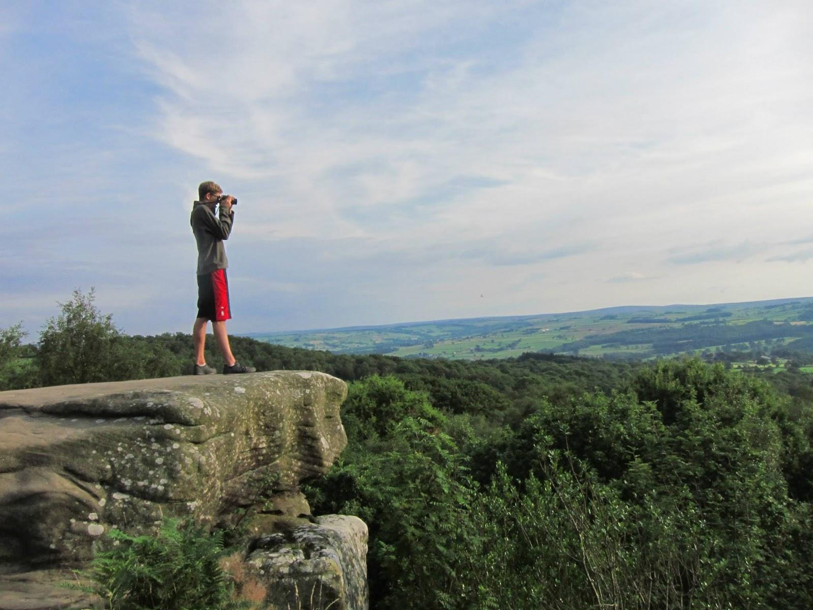 Joven sobre una roca oteando el paraje con unos prismáticos.