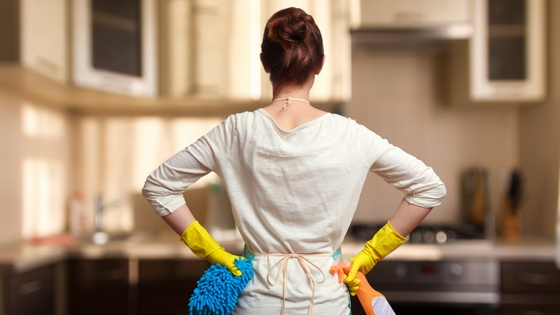 woman wearing cleaning gloves stands with hands on her hips in front of a kitchen counter