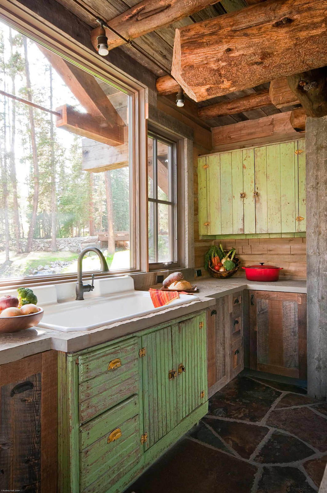 Old rustic cabin country farmhouse kitchen with mismatched green and dark wood cabinets, stone floor and farmhouse sink