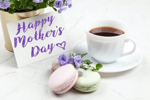 Dzień Matki - filiżanka kawy, laurka, ciastka-makaroniki i kwiaty. Wszystko stoi na białym obrusie.