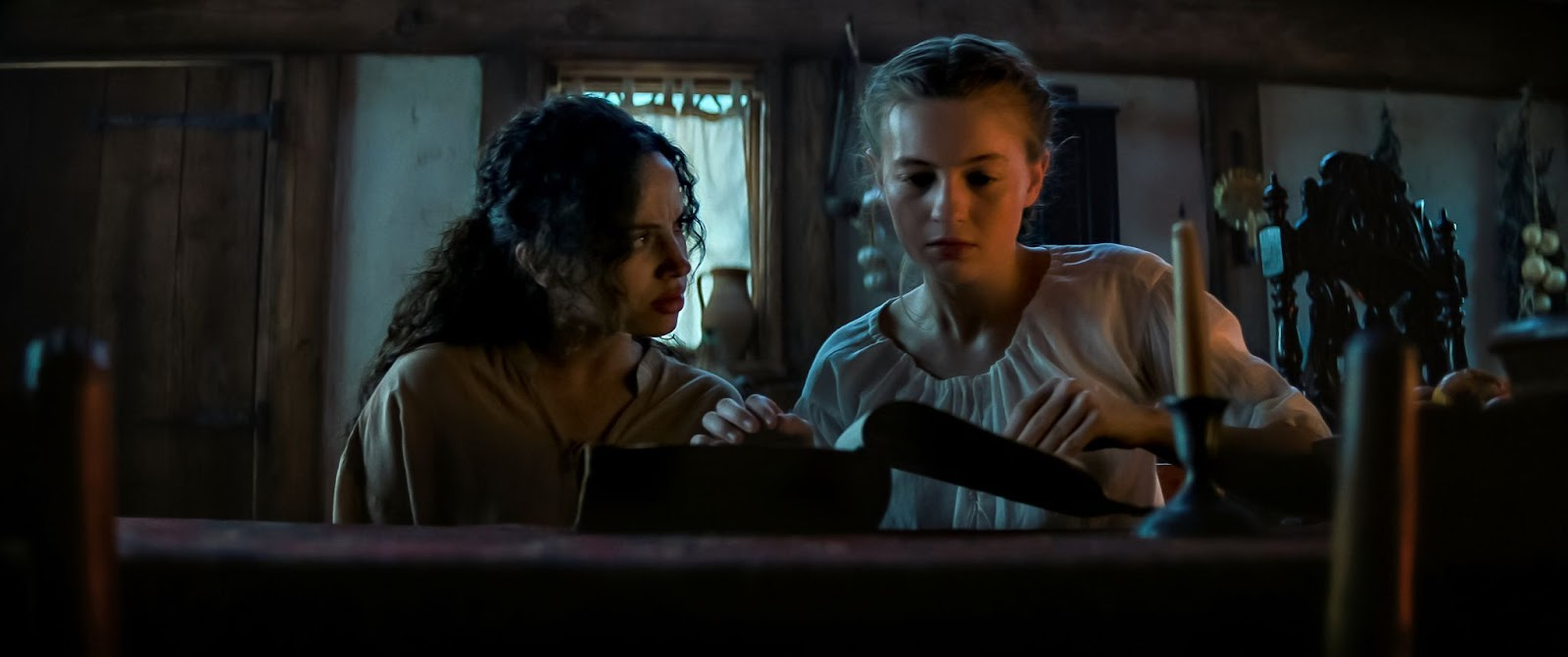 From left, Madeira as Sarah Fier and Welch as Hannah. The girls stand in a darkened room, Hannah opening a thick old book. She looks down at the pages as Sarah watches her, looking worried. Courtesy of Netflix.