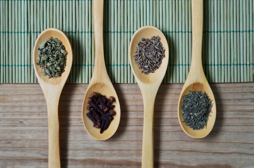 Brown Wooden Spoon With Herbs on Top of Green Bamboo Mat and Brown Wooden Surface