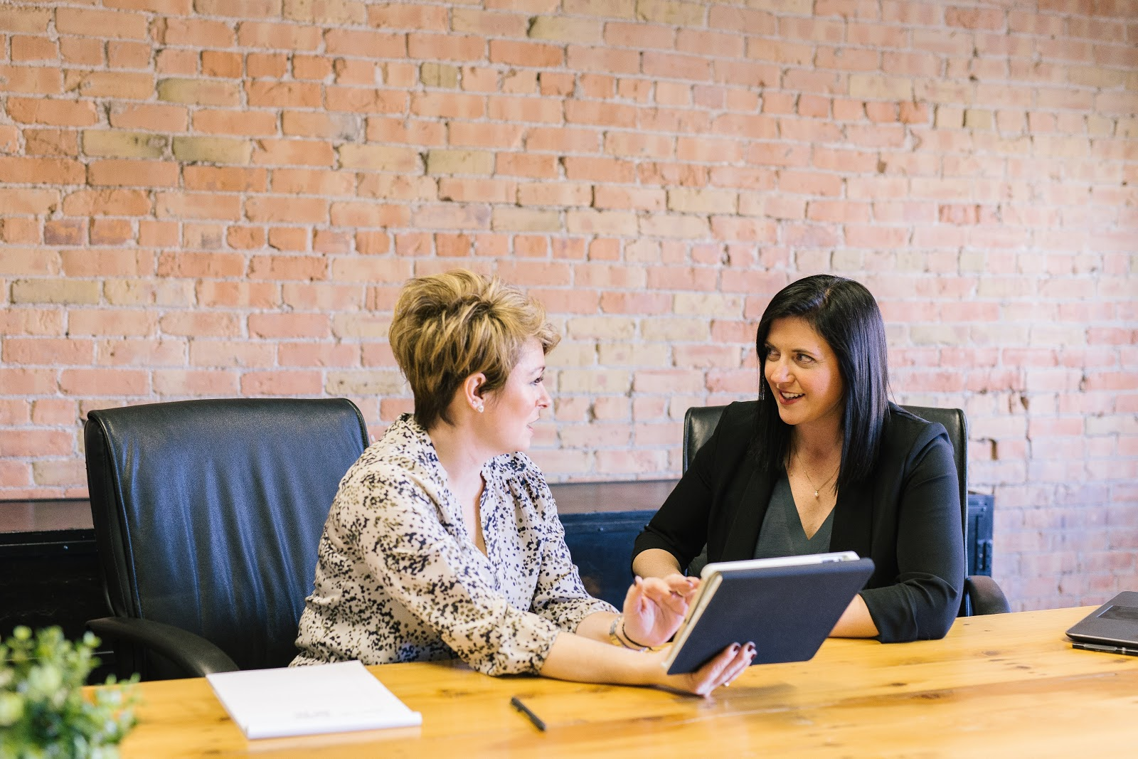 Two women in black leather desk chairs sitting at wooden meeting table