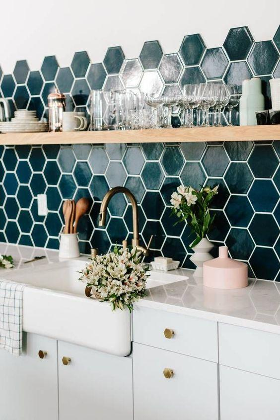 Cozinha com revestimento hexagonal em meia parede verde e outra metade pintada de branco, armários e bancada da pia branca, com vasos de plantas decorativos e prateleira com louças expostas.