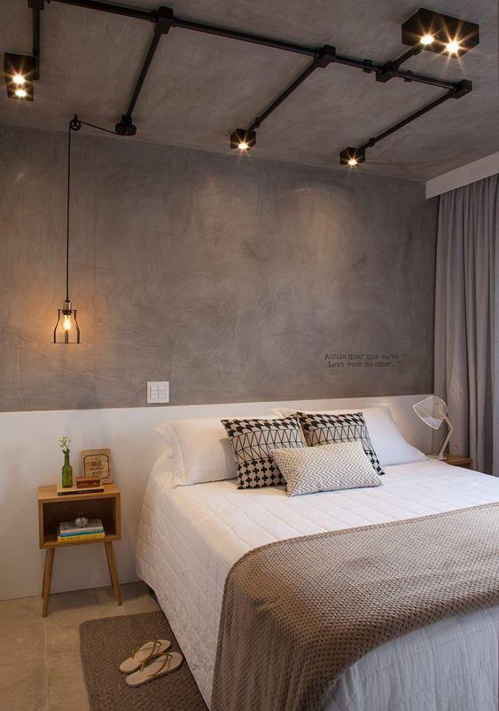 Quarto com pintura na parede substituindo cabeceira, meia parede branca e cimento queimado, piso em tom neutro e criado mudo de madeira.