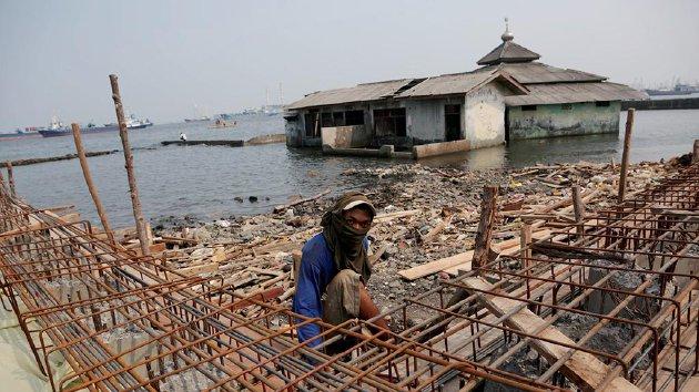 Pekerja membangun tanggul laut di pesisir Muara Baru, Penjaringan, Jakarta Utara, Senin (30/11). Tanggul laut yang dibangun oleh Pemerintah Provinsi DKI Jakarta itu untuk meminimalisir banjir rob yang terus meluas akibat penurunan muka tanah serta peningkatan muka air laut.