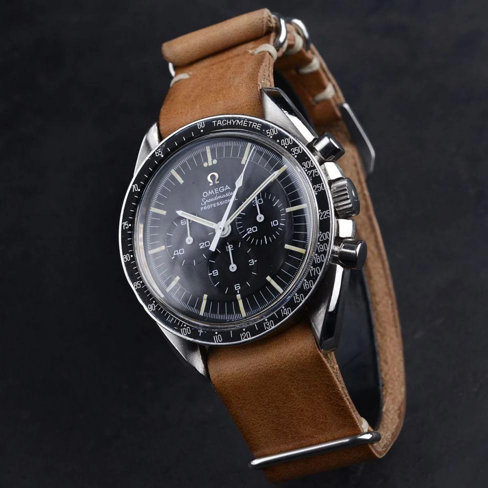 A close up of an omega watch on a leather strap